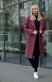 Junge stilvolle schöne frau, die in der straße geht und mantel, mode-outfit, herbsttrend trägt.
