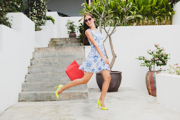 Junge stilvolle schöne frau im blau bedruckten kleid, rote tasche, sonnenbrille, fröhliche stimmung, mode-outfit, trendige kleidung, lächeln, sommer, accessoires, verspielt, zu fuß, laufen auf gelben schuhen mit hohen absätzen