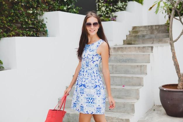 Junge stilvolle schöne frau im blau bedruckten kleid, rote tasche, sonnenbrille, fröhliche stimmung, modisches outfit, trendige kleidung, lächelnd, sommer, accessoires