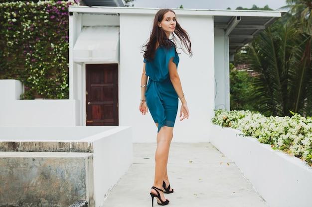 Junge stilvolle schöne frau im blauen kleid, sommermodetrend, urlaub, garten, tropische hotelterrasse, lächelnd, gehend, lange beine, absätze