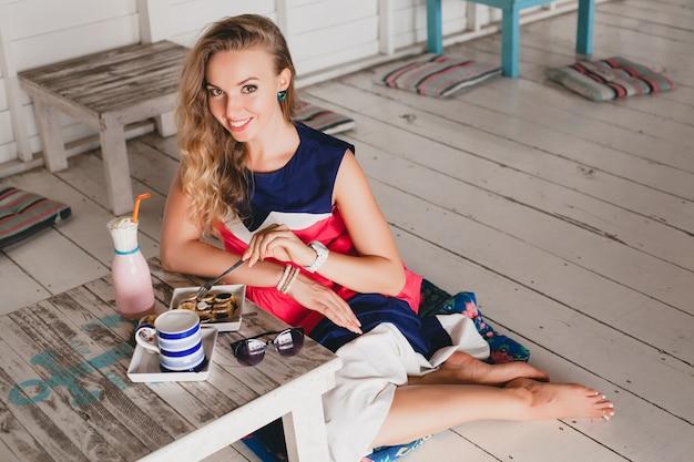 Junge stilvolle schöne frau im seecafé, essen pfannkuchen, cocktail smoothie, sonnenbrille, flirty, resort-stil, modisches outfit, lächeln, marinefarben kleid