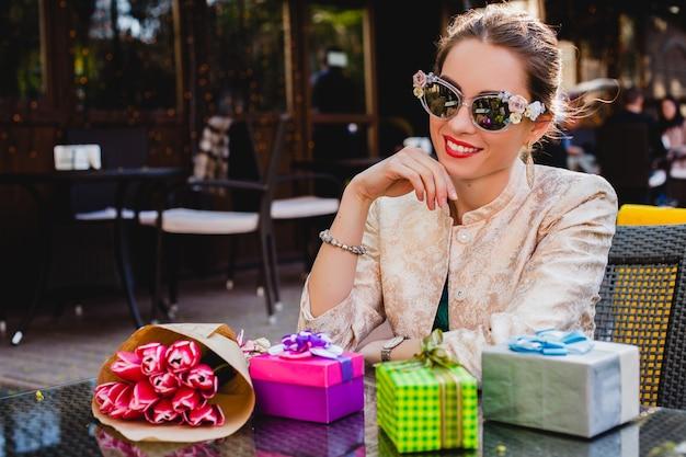 Junge stilvolle schöne frau in der mode-sonnenbrille, die am café sitzt
