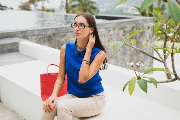 Junge stilvolle schöne frau, sommermodetrend, blaue bluse, rote tasche, brille, tropisches villenresort, urlaub, flirty