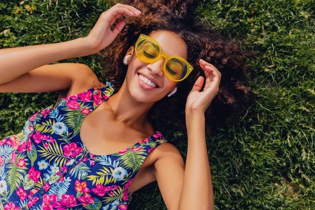 Junge stilvolle schwarze frau, die musik auf kabellosen kopfhörern hört, die spaß haben, auf gras im park liegend, sommermodeart, buntes hipster-outfit, ansicht von oben