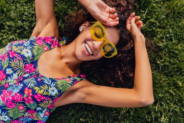 Junge stilvolle schwarze frau, die musik auf kabellosen kopfhörern hört, die spaß im park, sommermodeart, buntes hipster-outfit haben, auf gras liegend, ansicht von oben