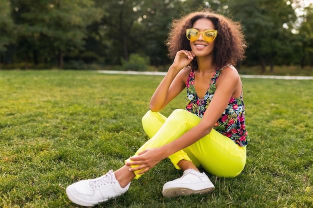 Junge stilvolle schwarze frau, die spaß im park-sommermodenstil, buntes hipster-outfit hat, das auf gras sitzt