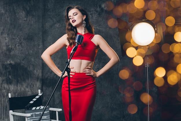 Junge stilvolle sexy frau auf kino hinter der bühne, feiern, rotes satinabendkleid