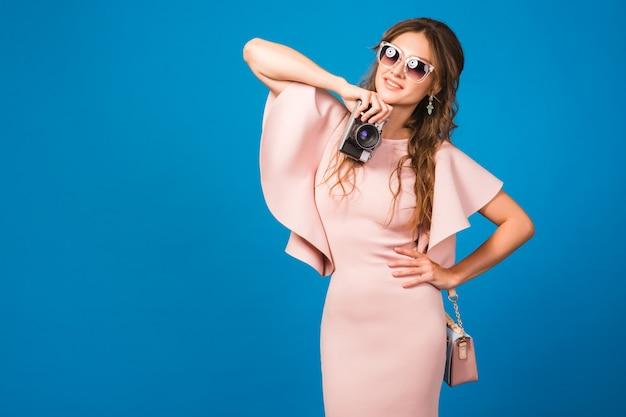 Junge stilvolle sexy frau im rosa luxuskleid, sommermodetrend, schicker stil, sonnenbrille, fotografieren auf vintage-kamera