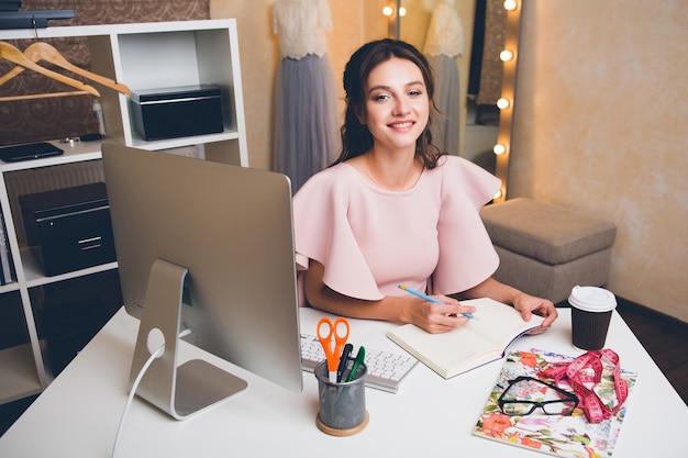 Junge stilvolle sexy frau im rosa luxuskleid, sommertrend, schicker stil, modedesigner, der im büro am computer arbeitet