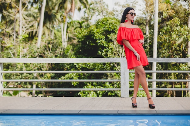 Junge stilvolle sexy frau im roten sommerkleid stehend auf terrasse im tropischen hotel, palmenhintergrund, langes schwarzes haar, sonnenbrille, ethnische ohrringe, sonnenbrille, die nach vorne schauen, schuhe mit hohen absätzen