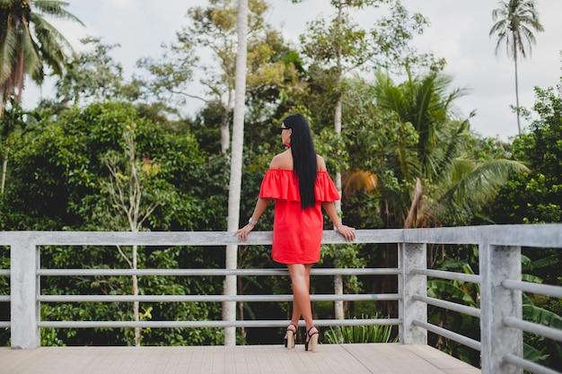 Junge stilvolle sexy frau im roten sommerkleid stehend auf terrasse im tropischen hotel, palmenhintergrund, langes schwarzes haar, sonnenbrille, ethnische ohrringe, sonnenbrille, die sich freuen