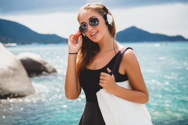 Junge stilvolle sexy hipster-frau mit einer einkaufstasche während des urlaubs, fliegersonnenbrille, kopfhörer, musik hören, glücklich, sonne genießen, tropische insel blaue lagunenlandschaft