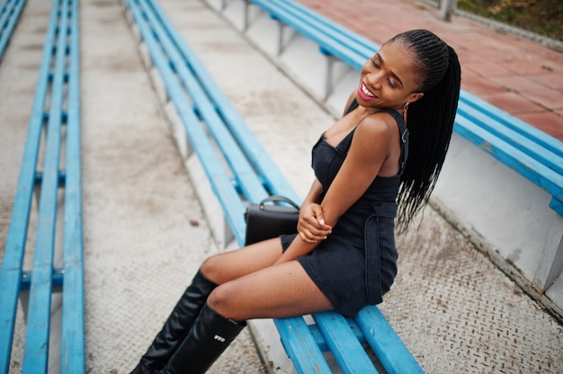 Junge stilvolle sexy schöne afroamerikanerfrau in der straße an den stadion tribünen, auf schwarz tragend.