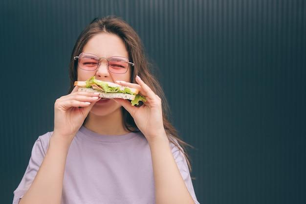 Junge stilvolle trendige frau, die ein stück sandwich beißt und mahlzeit genießt