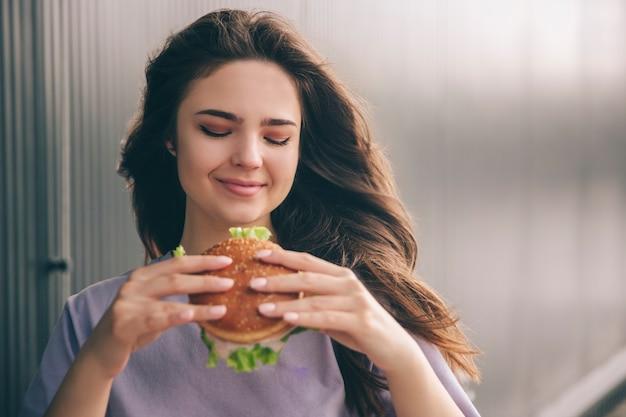 Junge stilvolle trendige frau, die leckeren köstlichen burger in den händen betrachtet