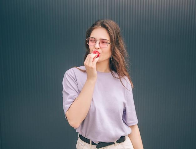 Junge stilvolle trendige frau, die rote erdbeere isst und aufwirft