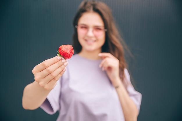 Junge stilvolle trendige frau lokalisiert über grauem blauem hintergrund. unscharfer hintergrund der frau, die rote erdbeere in der hand und im lächeln hält. zufällige frau, die vor der kamera aufwirft.