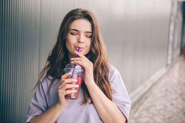 Junge stilvolle trendige frau steht allein draußen und trinkt limonade durch plastikstroh