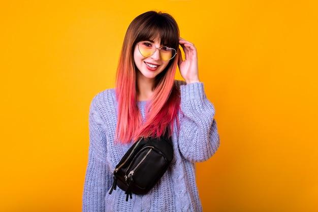 Junge stilvolle wundervolle hipster-frau mit langen ombre fuchsia-haaren, die an gelber wand, frühlingsschwingungen, weichen pastellfarben, sonnenbrille mit vintage-herz und trendiger gürteltasche posieren.