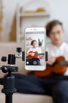 Junge stimmt gitarre, bevor er gitarre spielt, musik zu hause unterrichtet, hübscher junge stimmt gitarre, bevor er gitarre spielt, musik zu hause unterrichten. schüler stimmt ein musikinstrument, online-unterrichts-ukulele