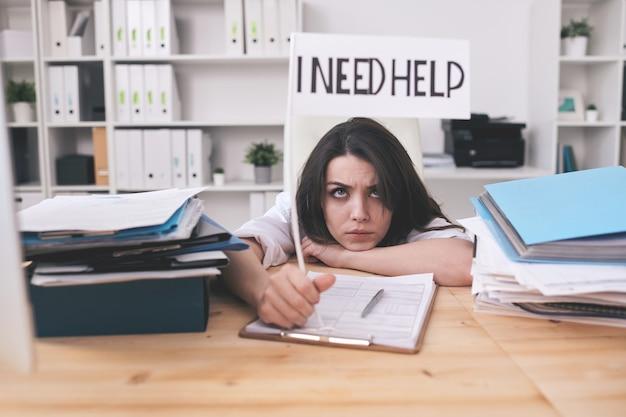 Junge stirnrunzelnde geschäftsfrau, die auf schreibtisch liegt und stock mit briefpapier hält und sagt, ich brauche hilfe bei der arbeit mit dokumenten
