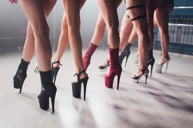 Junge striptease-tänzerin, die sich in high heels-schuhen auf der bühne im strip-nachtclub bewegt, pole dance.