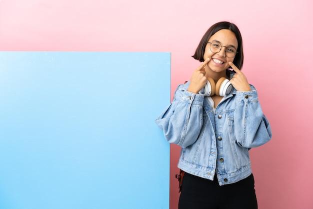 Junge student gemischte rasse frau mit einem großen banner über isoliertem hintergrund lächelnd mit einem glücklichen und angenehmen ausdruck
