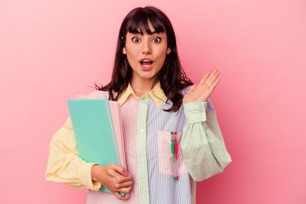 Junge student kaukasische frau, die bücher lokalisiert auf rosa hintergrund überrascht und schockiert hält.