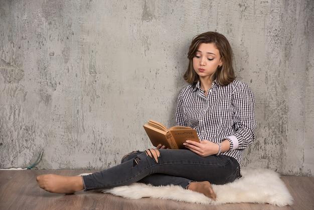 Junge student lesen buch sorgfältig im sitzen