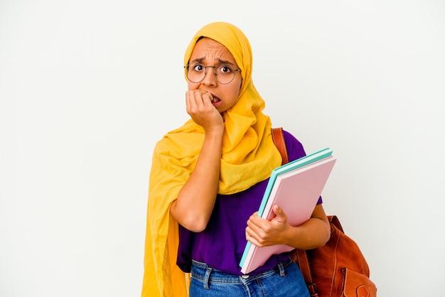 Junge student muslimische frau, die einen hijab trägt, der auf weißen wand isoliert fingernägel beißt, nervös und sehr ängstlich