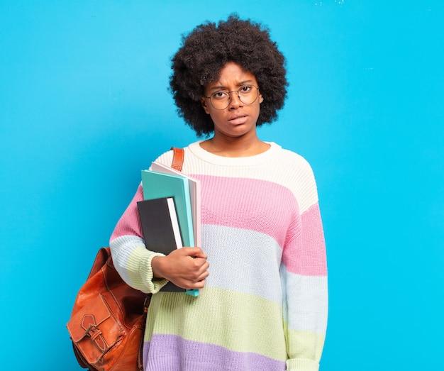 Junge studenten-afro-frau, die sich verwirrt und verwirrt fühlt, mit einem stummen, fassungslosen ausdruck, der etwas unerwartetes ansieht