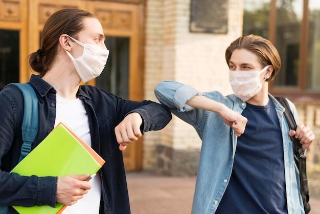 Junge studenten berühren die ellbogen an der universität