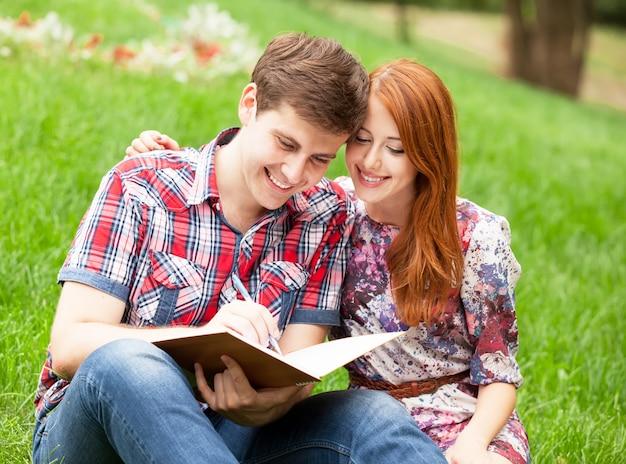 Junge studenten, die auf grünem gras mit anmerkungsbuch sitzen.