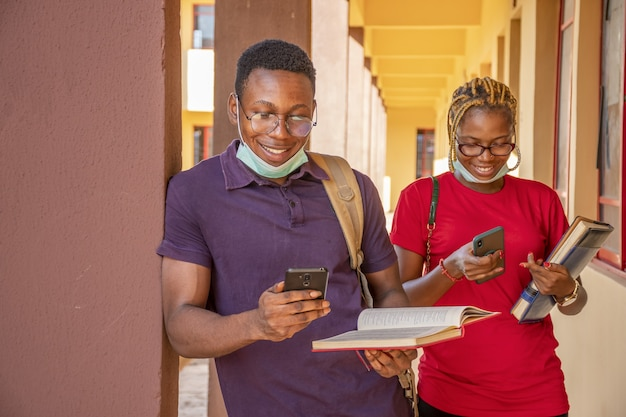Junge studenten, die gesichtsmasken tragen und bücher und telefone auf einem campus halten