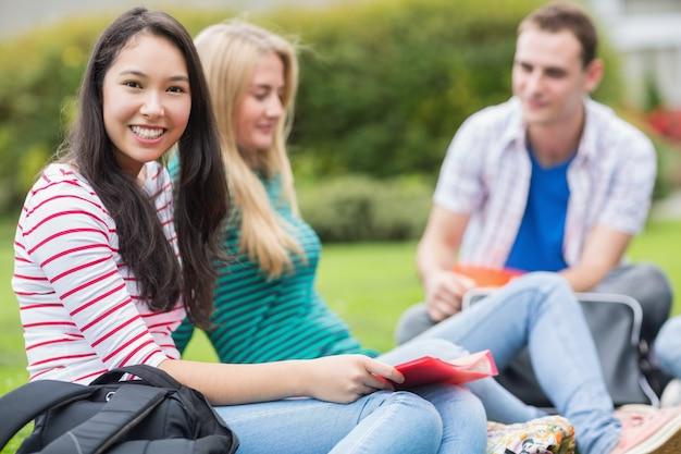 Junge studenten, die im park sitzen