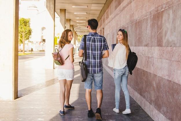 Junge studenten gehen an der universitätsmauer