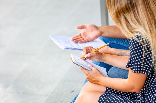 Junge studenten machen ihre hausaufgaben auf den stufen des universitätscampus