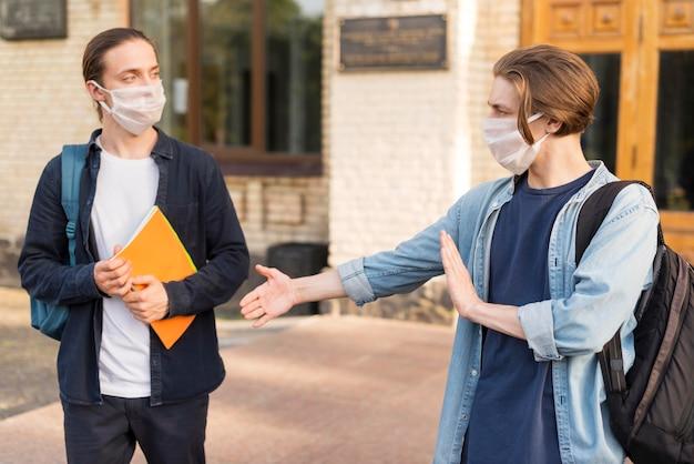 Junge studenten mit gesichtsmasken an der universität