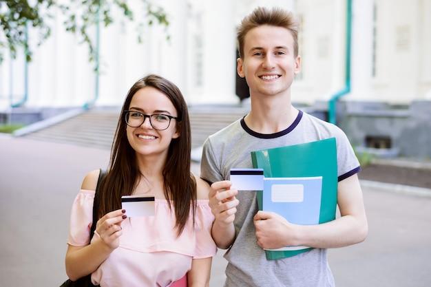 Junge studenten nähern sich universität mit büchern, den übungsbüchern, die kreditkarten halten und zur kamera lächeln