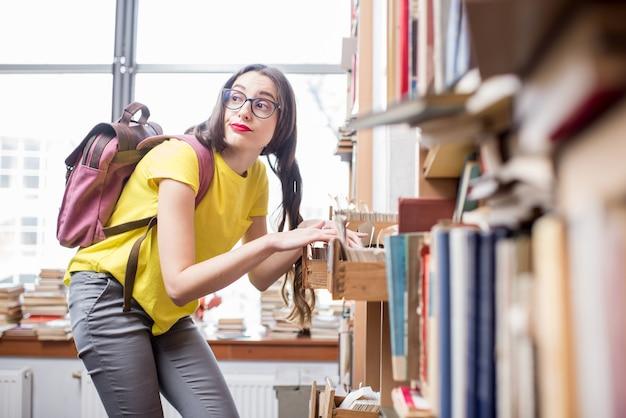 Junge studenten suchen bücher mit zettelkatalog in der alten bibliothek oder im archiv