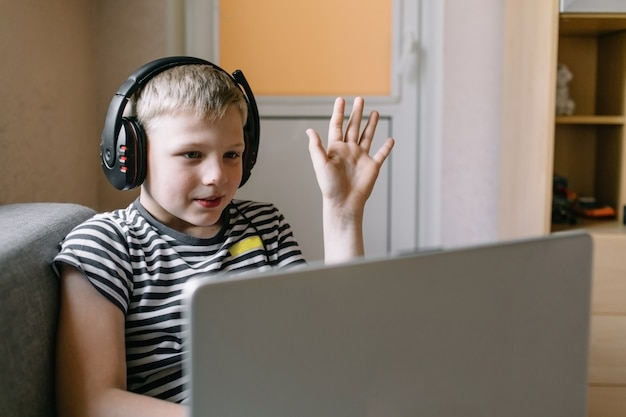 Junge studenten videokonferenz e-learning mit lehrer auf laptop im wohnzimmer zu hause. homeschooling und fernunterricht, online, bildung und internet.