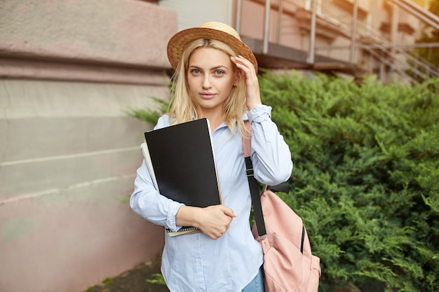 Junge studentenblondine in einem strohhut und in einem rosa rucksack, die notizbücher halten.