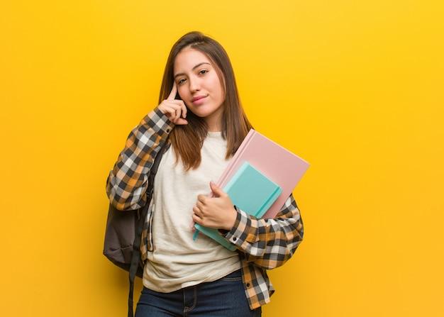 Junge studentenfrau, die an eine idee denkt