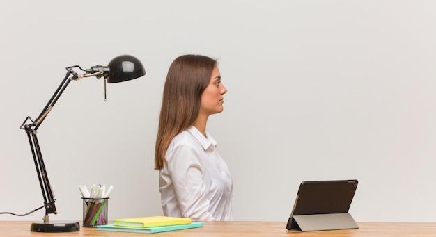 Junge studentenfrau, die an ihrem schreibtisch auf der seite schaut nach vorne arbeitet