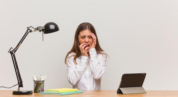 Junge studentenfrau, die an ihrem schreibtisch hoffnungslos und traurig arbeitet