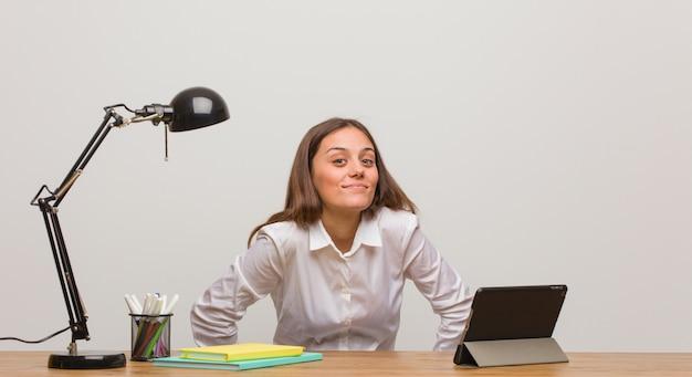 Junge studentenfrau, die an ihrem schreibtisch schilt jemand arbeitet, das sehr verärgert ist