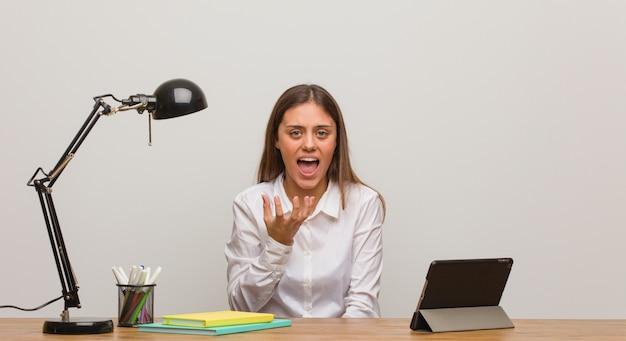 Junge studentenfrau, die an ihrem schreibtisch sehr erschrocken und ängstlich arbeitet