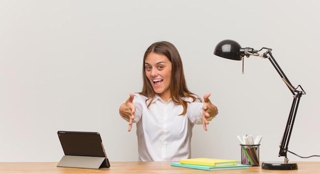 Junge studentenfrau, die an ihrem schreibtisch sehr glücklich arbeitet, der front eine umarmung gebend