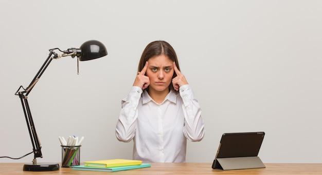 Junge studentenfrau, die an ihrem schreibtisch tut eine konzentrationsgeste arbeitet