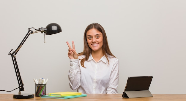 Junge studentenfrau, die an ihrem schreibtisch zeigt nummer zwei arbeitet
